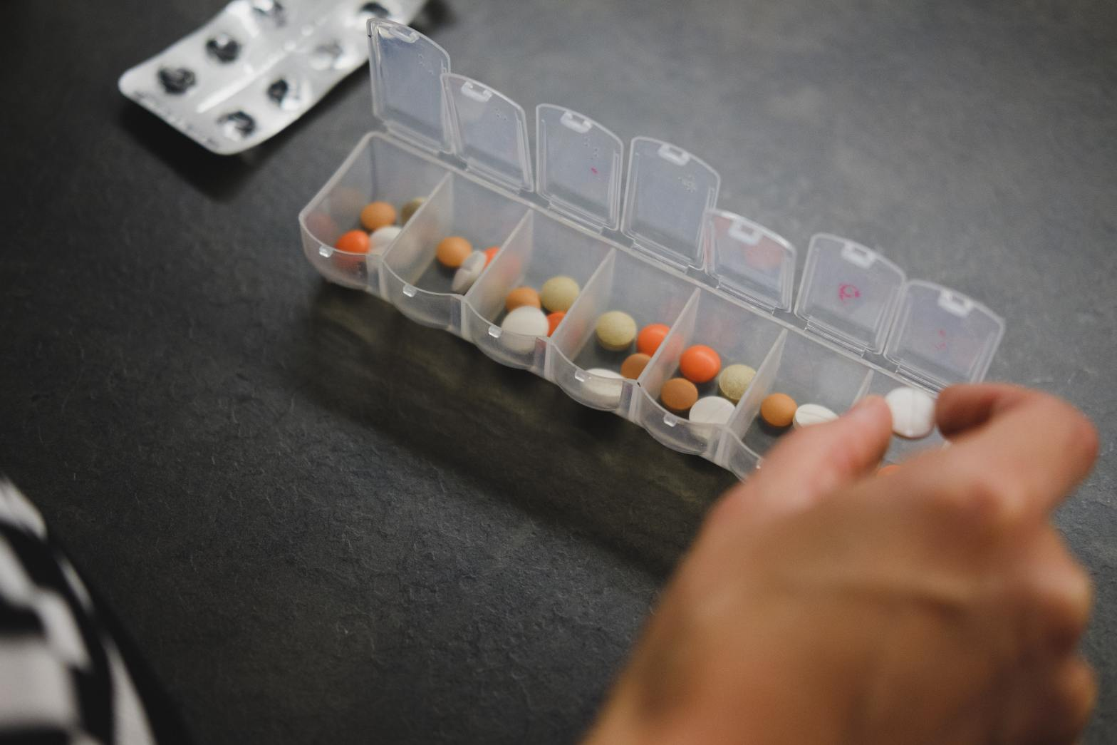 A person is filling their pill container with medication.