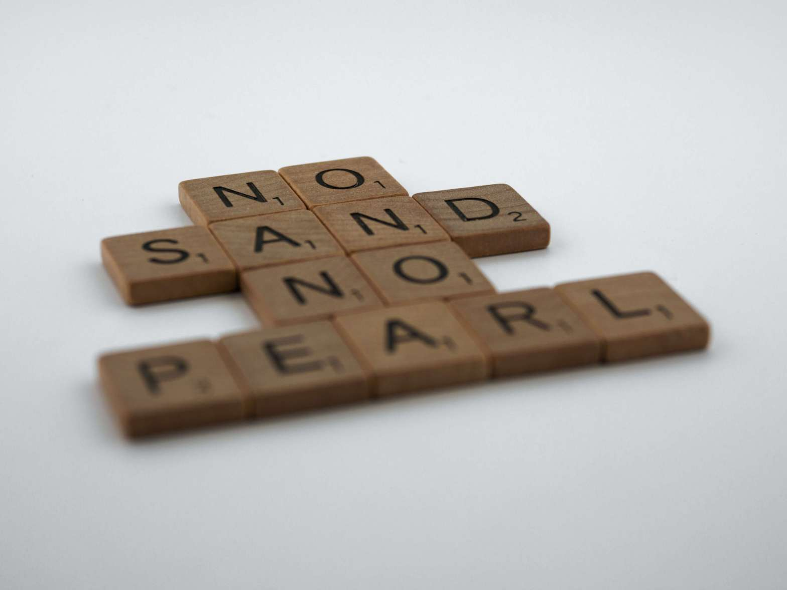 "Brown Scrabble letters that read ""No Sand No Pearl"""